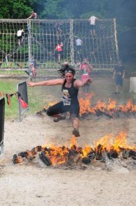 Jamie Wimberly jumping over fire in a Spartan event